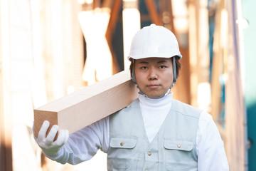 材木を担ぐ大工