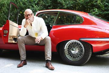 rauchender Mann sitzt im Sportwagen