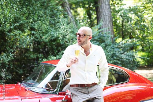 Mann mit Champagner und Sportwagen