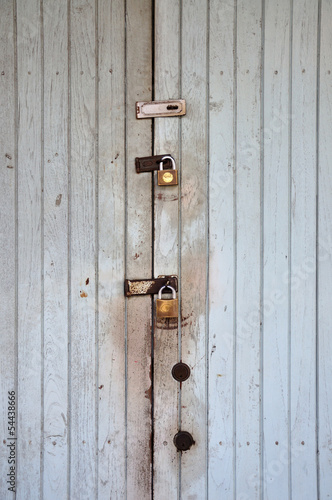 White grunge plywood classic door with padlocks.