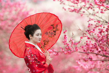 Asian style portrait of a woman with red umbrella