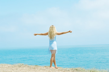 girl standing on the beach arms outstretched