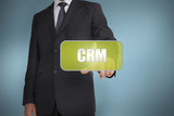 Businessman touching green tag with the word crm written on it