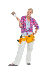 Happy woman holding paint brush wearing a tool belt