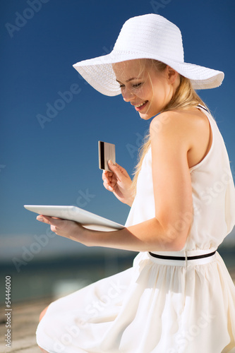 woman in hat doing online shopping outdoors
