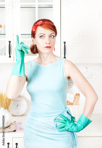 Beautiful housewife with rubber gloves showing finger