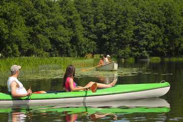 Young couple kayaking summertime  in the sunshine vacation