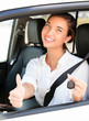 Happy girl in a car showing a key and thumb up gesture