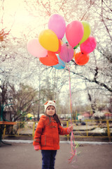 on nature walks in the park little girl with colorful balloons