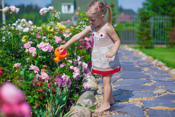 Adorable cute girl watering flowers with a watering can