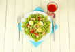 Caesar salad on white plate, on color wooden background