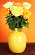 Beautiful bouquet of roses in vase on table on orange