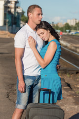 The girl and the man say goodbye at railway station