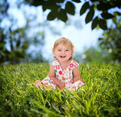 Beautiful little girl smiling on the grass