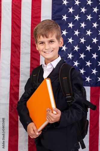 Ð¡ute schoolboy is holding a book against USA flag