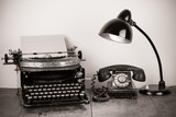 Vintage typewriter, old telephone, retro lamp on table