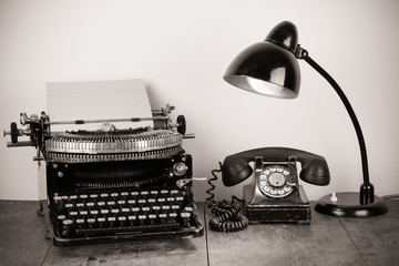 Vintage typewriter, old telephone, retro lamp on table