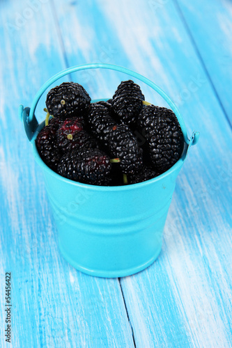 Ripe mulberries in bucket on wooden background