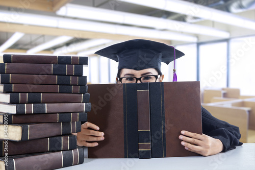 Young female bachelor covering her face with book in library