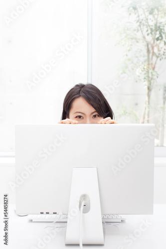 モニターの陰から覗く女性
