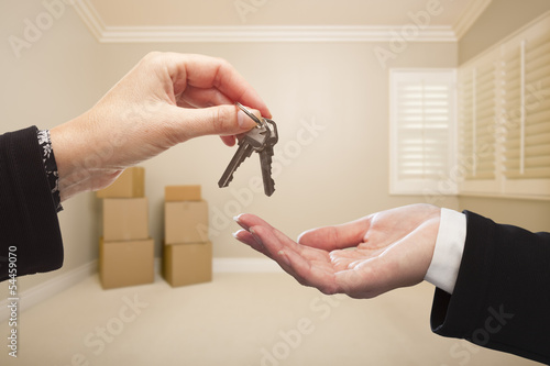 Woman Handing Over the House Keys Inside Empty Tan Room