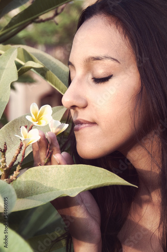 Portait of sensual young woman taking a smell at a blossom