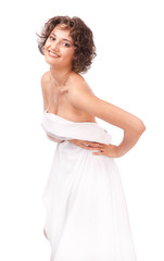 A smiling girl, clothed a white sheet on a white background