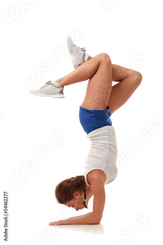 Young pretty fitness model in handstand