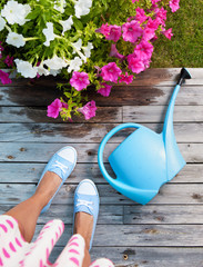 Woman with watering can and flowers on a patio deck