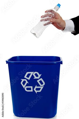 Hand putting a water bottle in a recylce bin