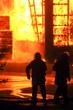 Feuerwehrmänner vor brennender Halle