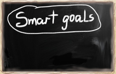 """Smart goals"" handwritten with white chalk on a blackboard"