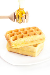 Belgian waffles on a plate, stick for honey and honey isolated o