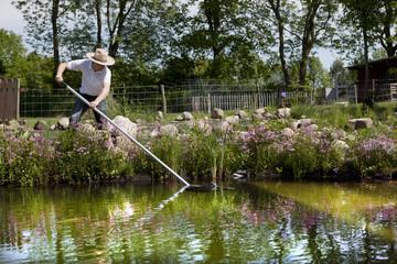 Gärtner mit Strohhut reinigt seinen Teich