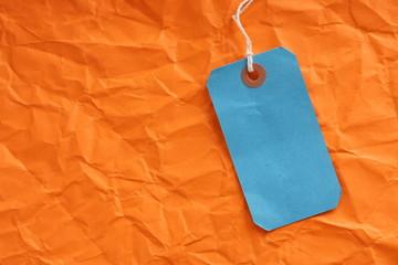 Blue Paper Luggage Tag on Orange Background