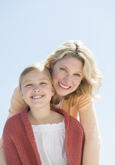 Mother And Daughter Smiling Together Against Clear Blue Sky