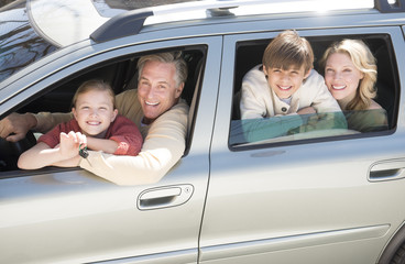 Girl Showing Car Keys While Sitting With Family In Car