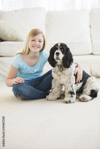 Cute Girl Sitting With Pet Dog In Living Room