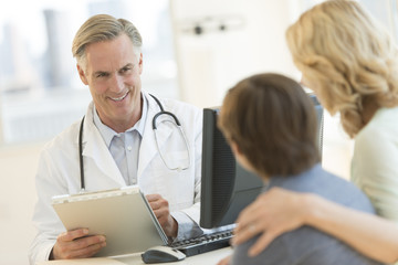 Doctor Explaining Report To Son And Mother At Clinic