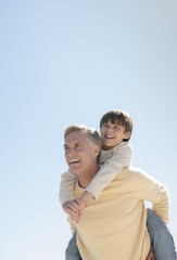 Father Giving Piggyback Ride To Son Against Clear Blue Sky