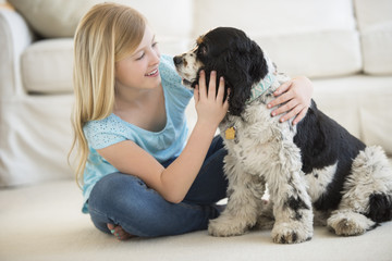 Girl Playing With Pet Dog In Living Room