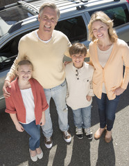 Loving Parents And Children Standing Against Car