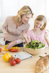 Girl Assisting Mother In Preparing Salad At Counter