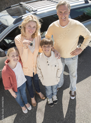 Woman Showing Keys While Standing With Family Against Car