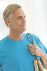 Man With Jump Rope Looking Away In Health Club