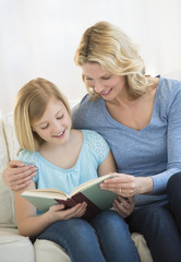 Mother And Daughter Reading Book Together At Home