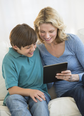 Mother And Son Using Digital Tablet Together At Home