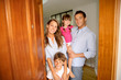 Family standing on the entrance door of new home