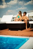 Sexy young couple relaxing near pool on a beach bed