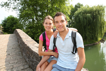 Couple on a rambling day sitting on a roman bridge